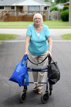 struggling: senior woman and walker overloaded with shopping bags
