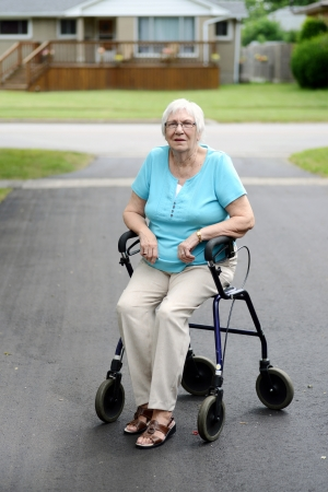 Tired senior woman sitting on walker photo