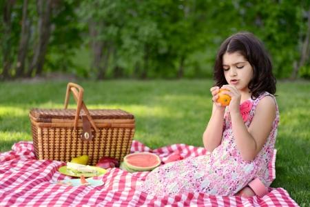 child peeling orange at picnic photo