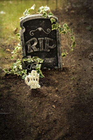Skeleton hand coming out of grave photo