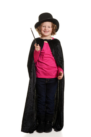 stovepipe hat: laughing little girl dressed up as magician Stock Photo