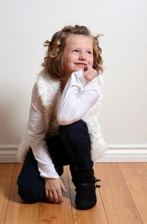 girl boots: happy little girl kneeling Stock Photo