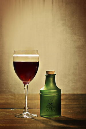 glass red wine with poison bottle photo