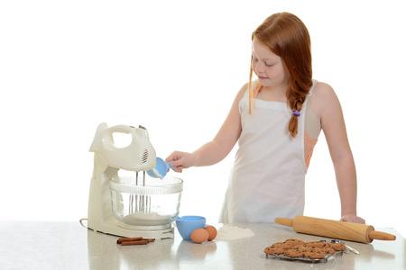 mixer: girl adding flour to stand mixer
