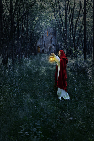 woman with lantern in forest and castle photo