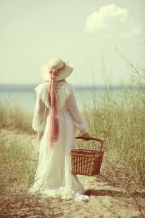 vestidos antiguos: Mujer de la vendimia en la playa con la cesta de picnic