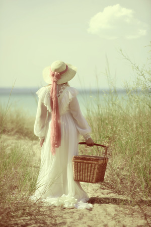 vintage woman at the beach with picnic basket