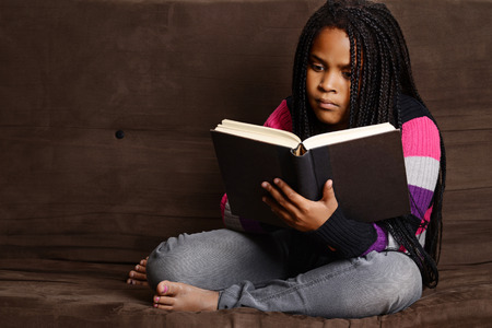 cornrows: child reading book sitting on couch