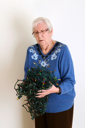 decorating christmas tree: senior confused with tangled christmas lights