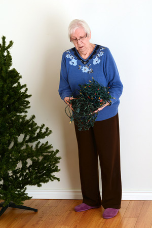 decorating christmas tree: senior trying to untangle christmas lights