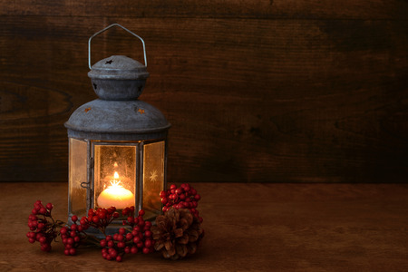 old barn in winter: antique lantern with red berries