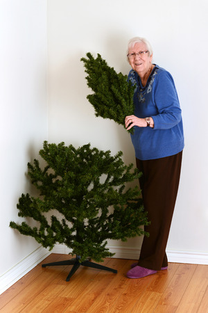 fake christmas tree: senior woman with fake christmas tree