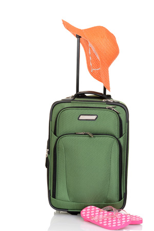 luggage pieces: green suitcase with hat and sandals Stock Photo