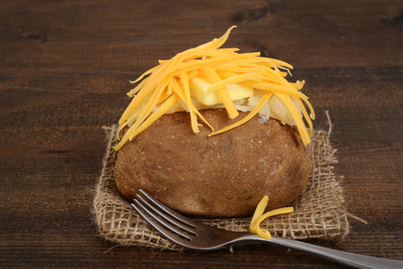 baked potato with cheese and butter Imagens