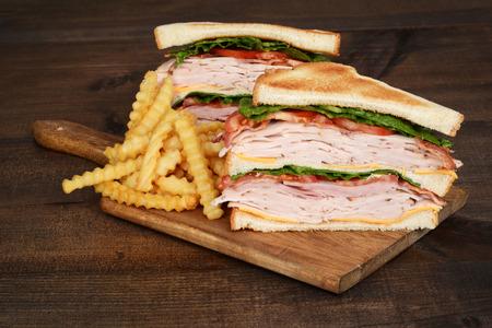 pollo a la brasa: tostado club sandwich de pollo con patatas fritas