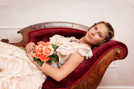 woman on couch: victorian woman with flowers on fainting couch Stock Photo