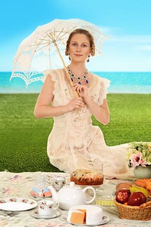 edwardian: young edwardian woman at picnic with umbrella Stock Photo