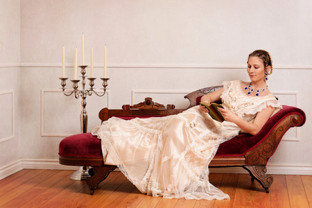 woman on couch: victorian woman reading book on fainting couch