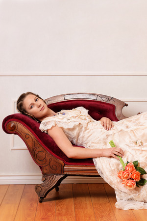 woman on couch: victorian woman laying on couch Stock Photo
