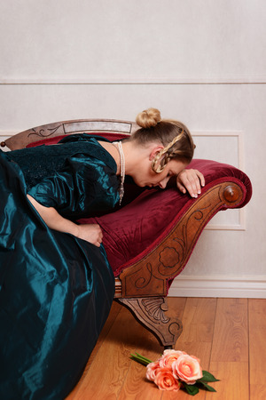 woman on couch: sad victorian woman on fainting couch