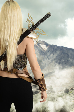back of female warrior looking at mountain 免版税图像