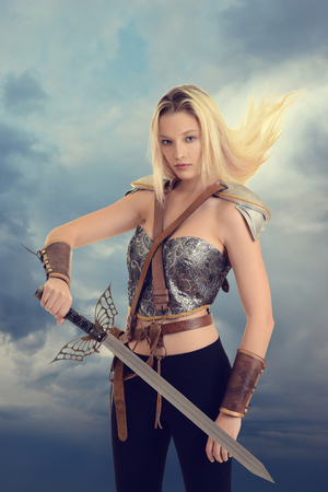 female warrior with sword and hair blowing in wind Stock Photo