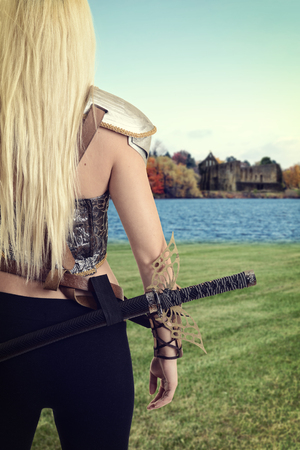 female warrior looking across a lake at castle