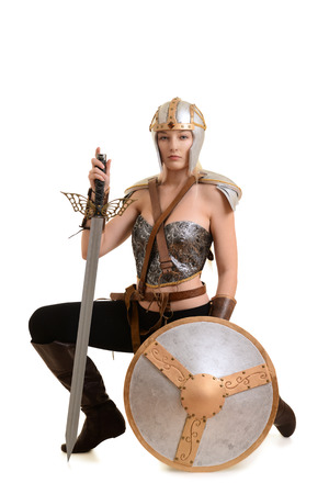 female warrior kneeling with sword and shield