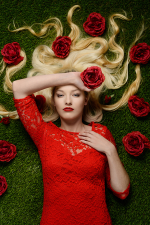 woman laying in grass wearing red dress holding  a rose