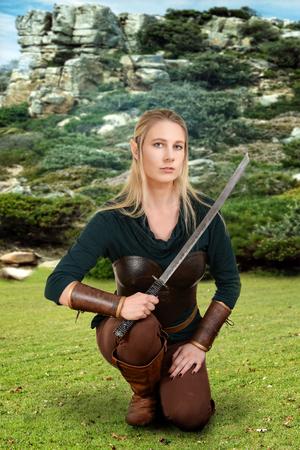 faerie: female wood elf kneeling in field Stock Photo