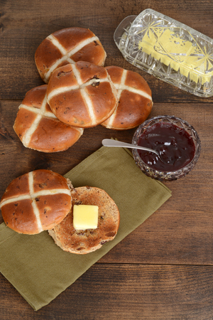 buttered: top view toasted hot cross bun with butter
