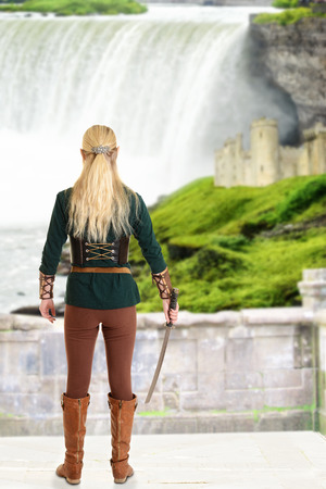 faerie: female elf with sword looking at waterfall Stock Photo