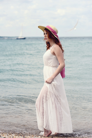 woman walking on the beach in white lace dress