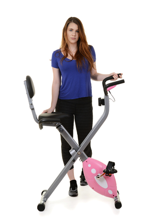 young woman standing by exercise bike