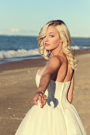 blonde woman in white dress follow me on beach Foto de archivo