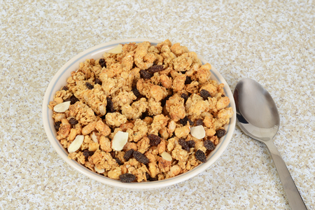 top view bowl of granola raisin almond cereal with a spoon
