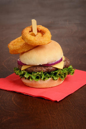 hamburger with onion rings on top with red napkin