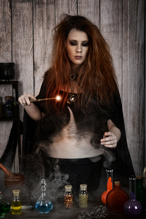 witch casting a magic spell into her cauldron potion