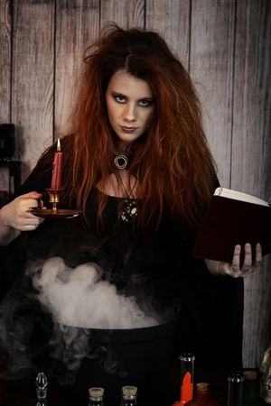 witch holding spell book and candle