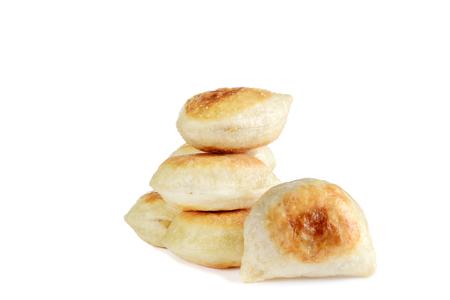 closeup pile of pierogies on white