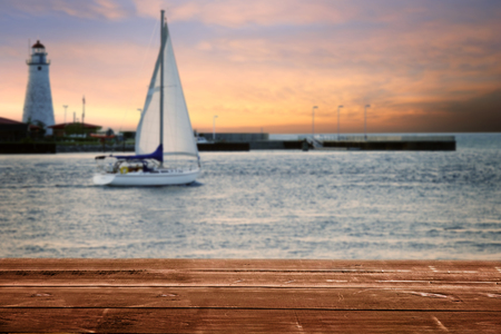 wood deck with sailboat and lighthouse at sunset