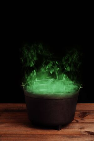 black halloween cauldron with green smoke
