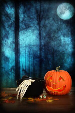 halloween pumpkin with skeleton hand and cauldron