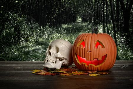 halloween pumpkin and skull in the evening on wood table
