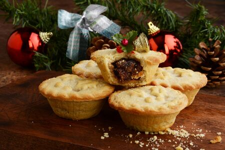 closeup pile of mincemeat pies with christmas ornaments