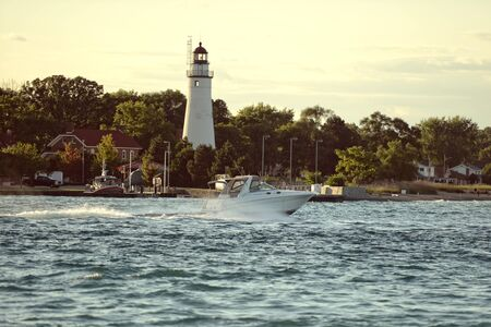 powerboat by lighthouse on the river