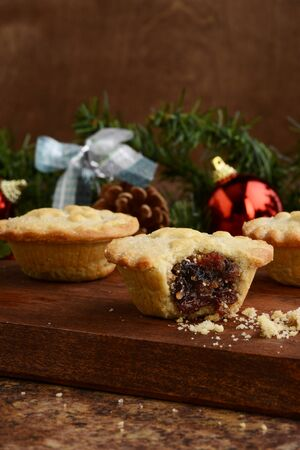 christmas mincemeat pie with bite on wood cutting board