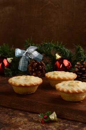 three mincemeat pies on wood cutting board