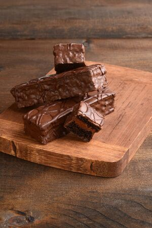 pile of chocolate cream filled bar cakes on cutting board
