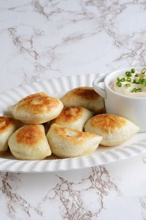 pierogies on a white platter with sour cream and spring onions Stock fotó